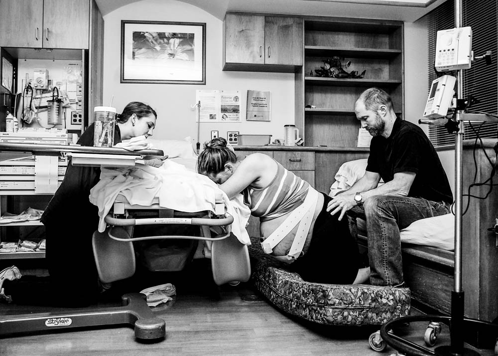Mom on hands and knees during labor at hospital. Bellingham birth photography.