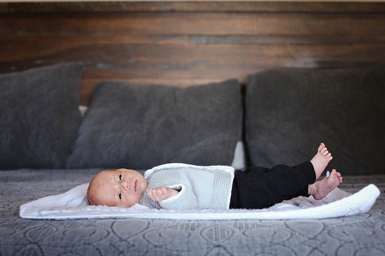 Newborn baby in handknit sweater looks at camera during newborn session. Bellingham, WA
