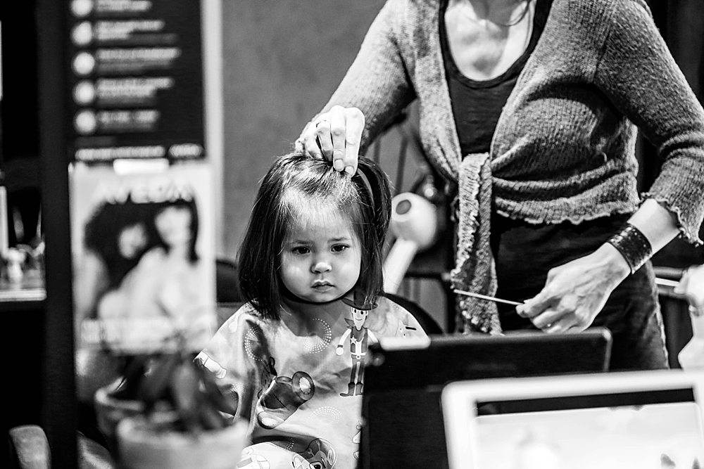 Toddler looking in mirror during haircut.