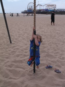 Noah tries to climb a rope on the beach.