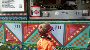 Noah stands at the hot dog kiosk.