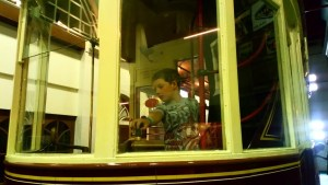 Noah pretends to drive a tram at the Street life museum.