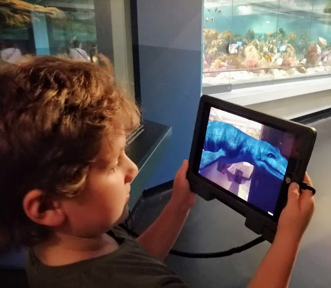Noah uses a tablet to look at an augmented reality view of what the prehistoric sea monsters looked like.