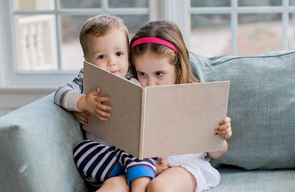 Boy and girl reading together on couch