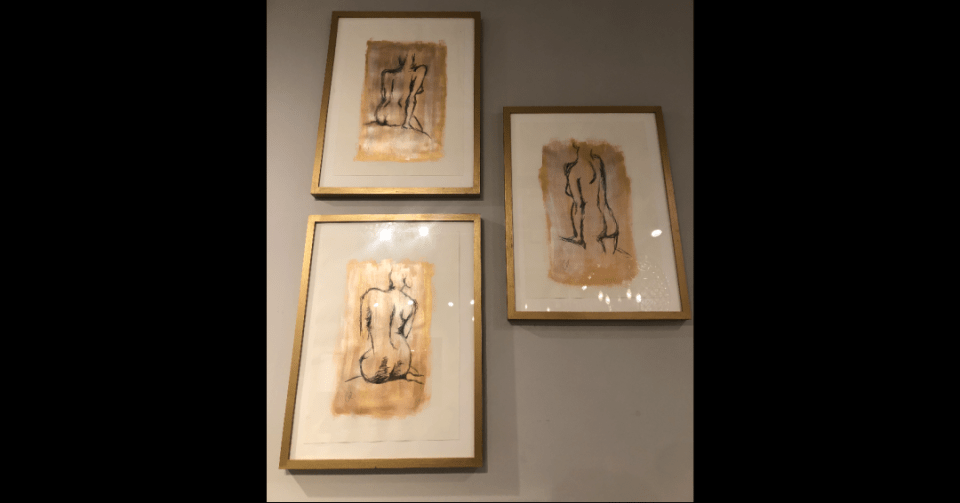 gold sitting nude paining displayed in showroom with other gold nude paintings by Eve