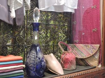 Window display of scarves, babouche, purses & a crystal decanter