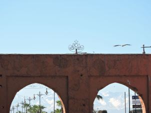 Ancient arches frame colonial street lamps & distant Atlas Mountains.