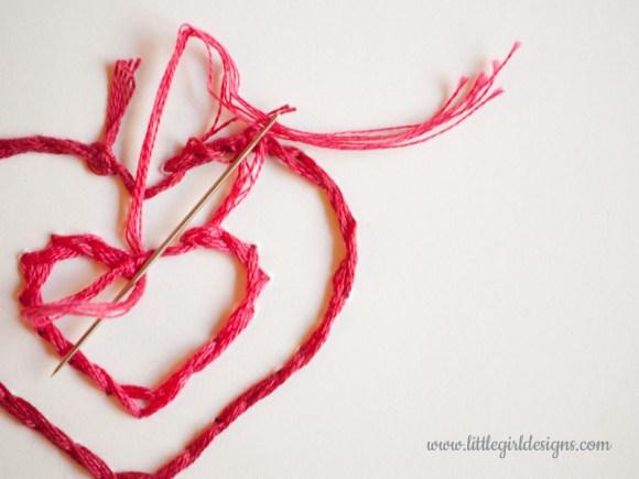 Hand-stitch a card closeup of finishing the heart stitchery