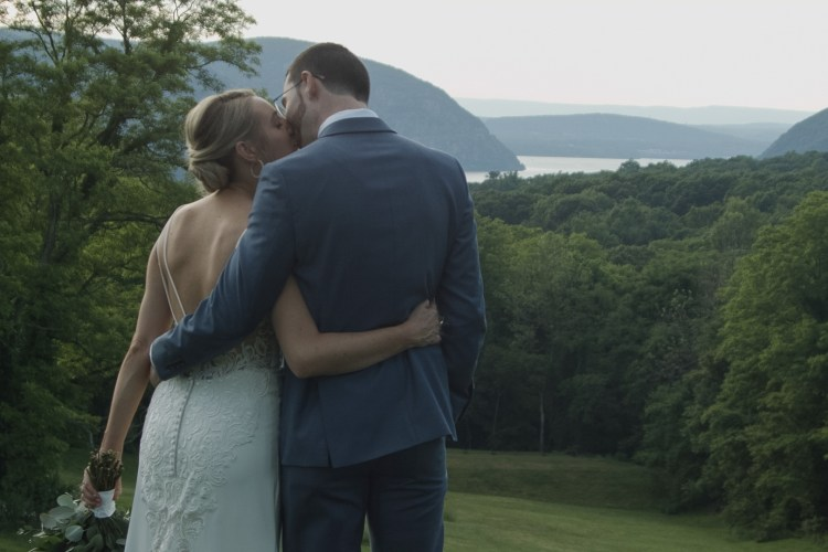 A married couple kissing in front of a field and the Hudson River
