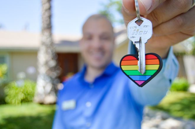 Smiling Airbnb host holding out a key with a rainbow heart keyring close to the camera