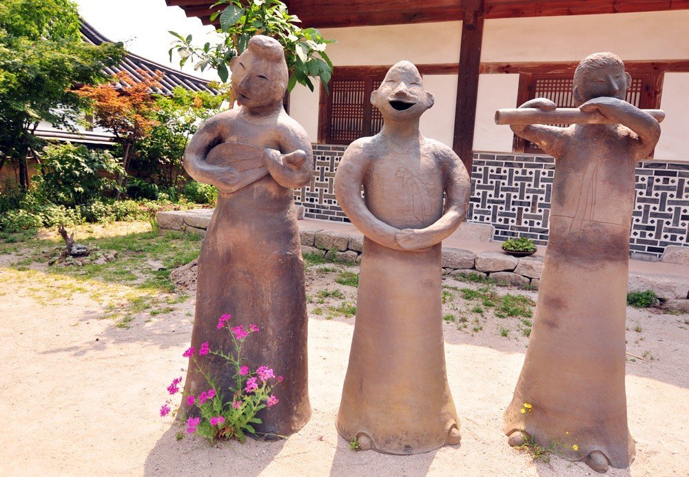 Statues happily welcome you to the Gyochon Traditional Hanok Village in Gyeongju.