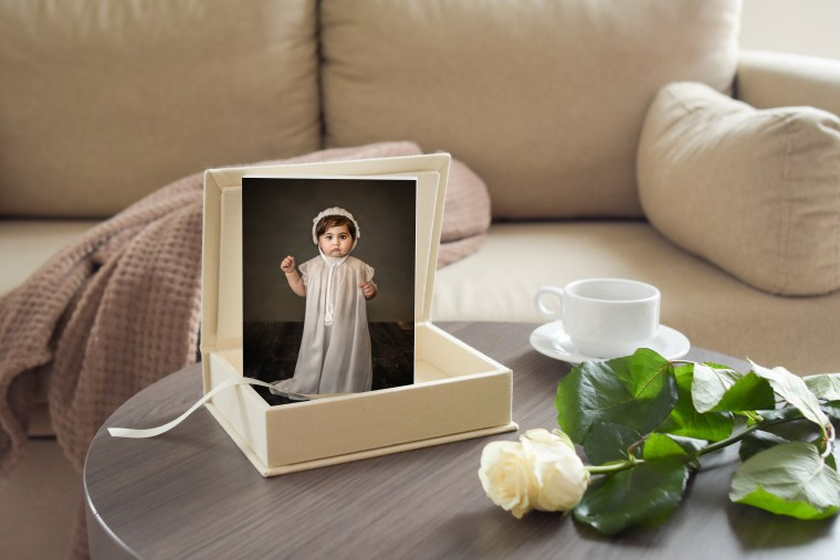 a folio box displaying a baby's fine art print from her first birthday photo session