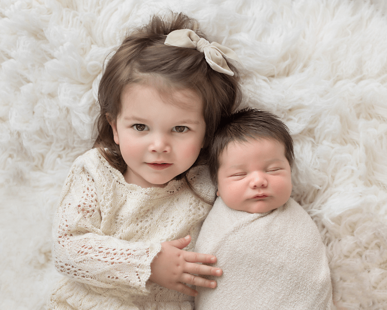 2 siblings laying on a cream rug during the baby's newborn photography session in Fresno, California