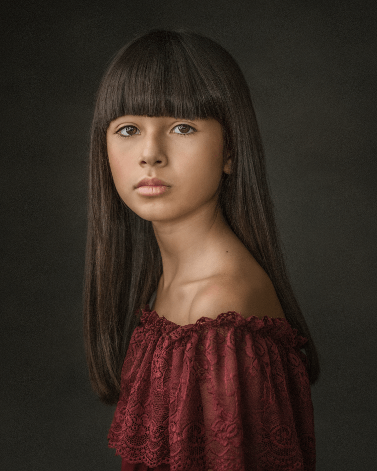 an 11 year old girl during a children photo session wearing a red dress.