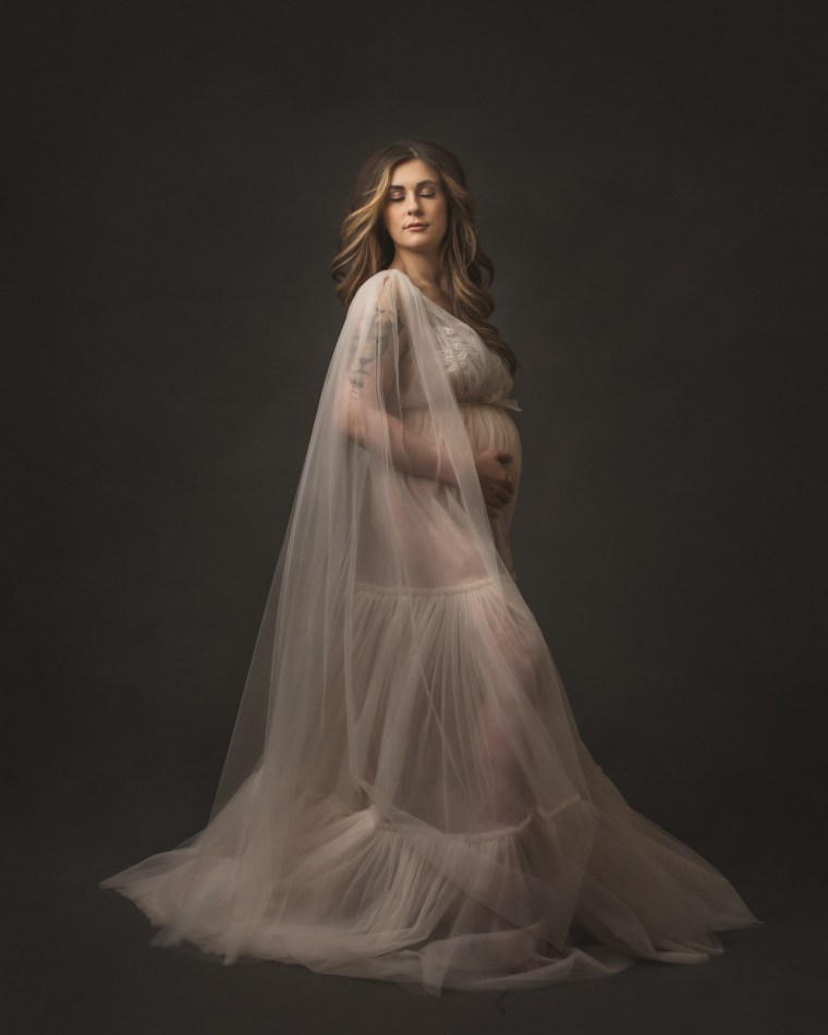 A pregnant mother wearing a couture ivory gown at 32 weeks pregnant.