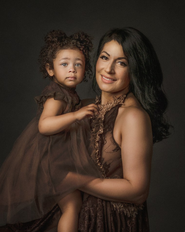 A mother and daughter wearing brown dresses and embracing