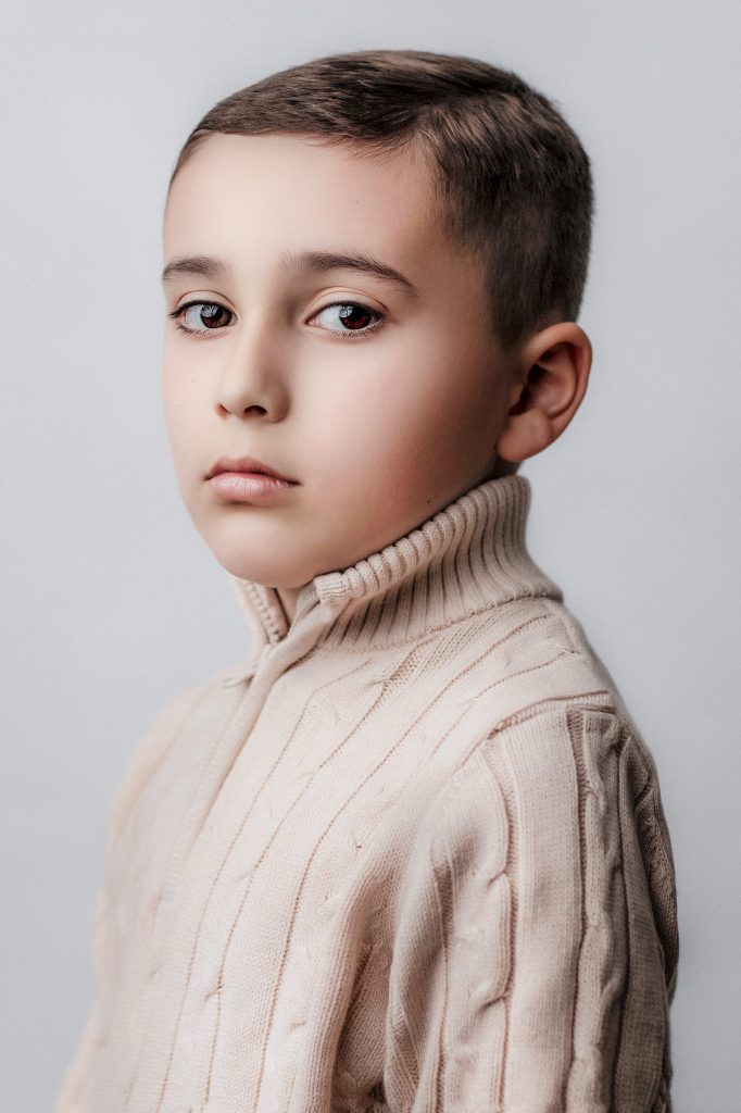 A young boy wearing a cream colored knit sweater during a photo session