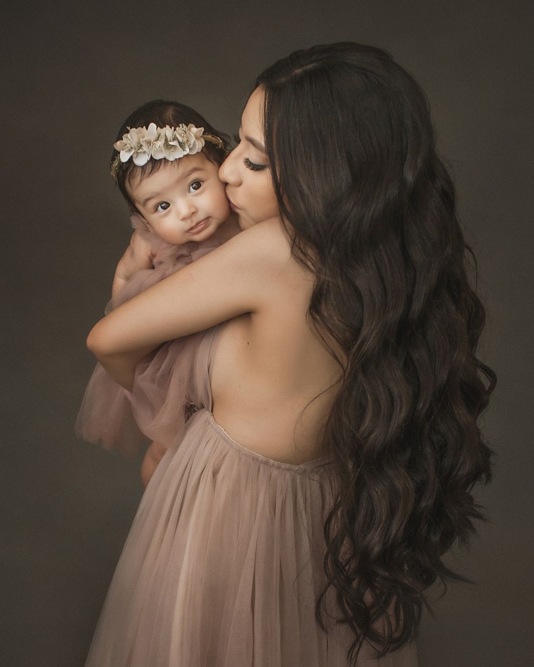 a mother wearing a tulle pink dress and giving her 5 month old daughter a kiss on her cheek