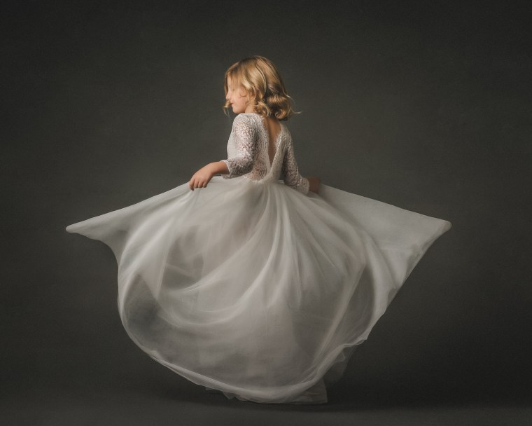 A 7 year old girl twirling in a long ivory tulle dress