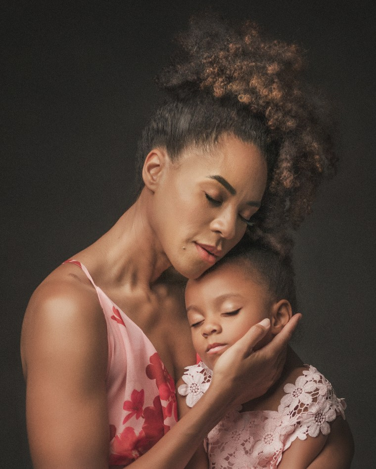 a mother wearing a pink floral dress embracing her 4 year old daughter