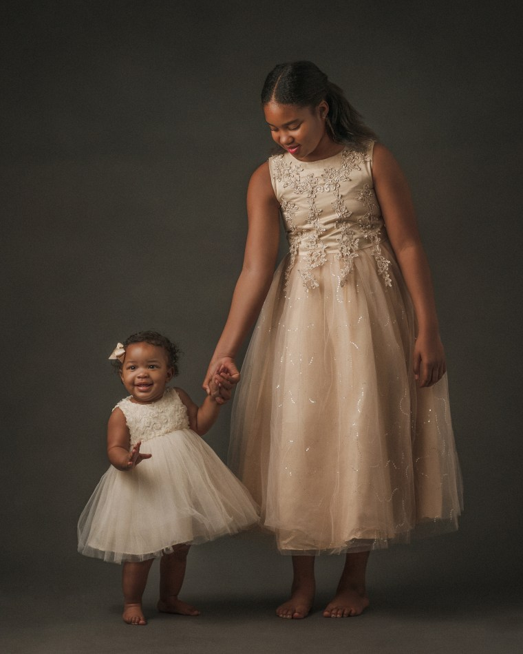 two sisters holding hands and laughing while wearing tulle dresses