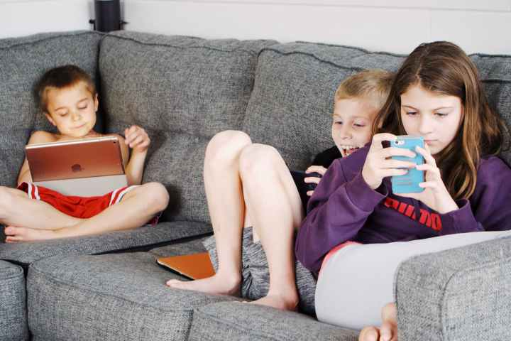 children lying on sofa and using gadgets