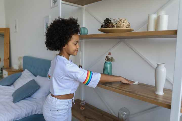 small girl cleaning shelf in apartment