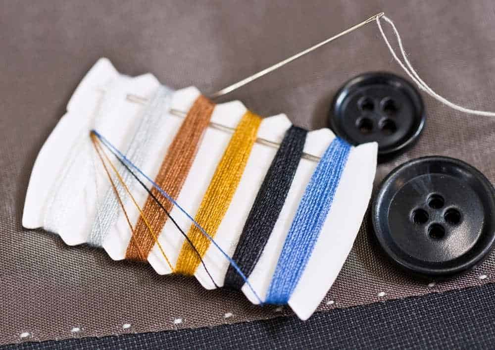 Image of coloured threads, needles and buttons. A sweing kit is a handy eco-friendly travel product.