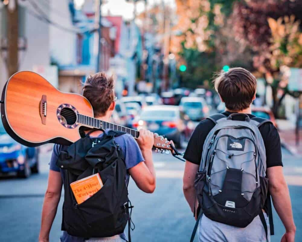 Two backpackers backpacking with a guitar