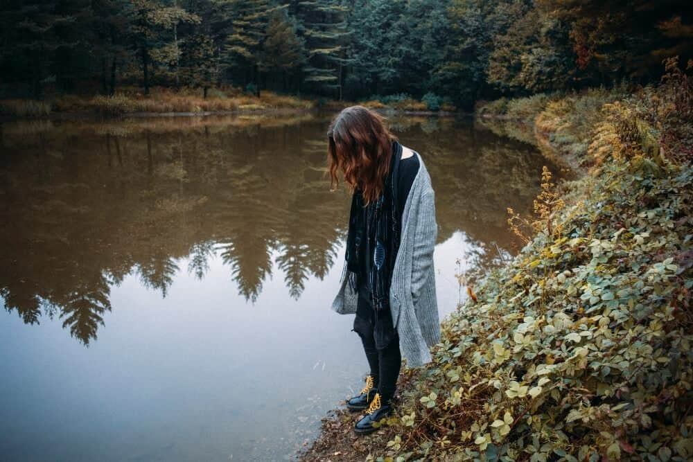 Woman walking by a lake for post-travel depression