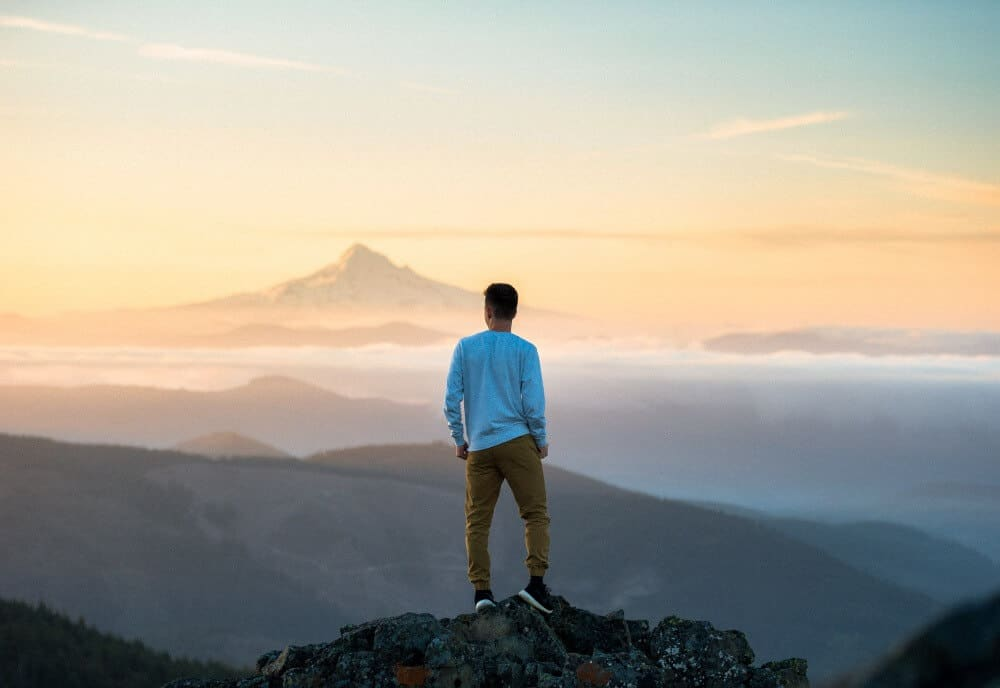 Man standing on top of mountain. Don't overthink it, it's the best way to overcome solo travel anxiety.