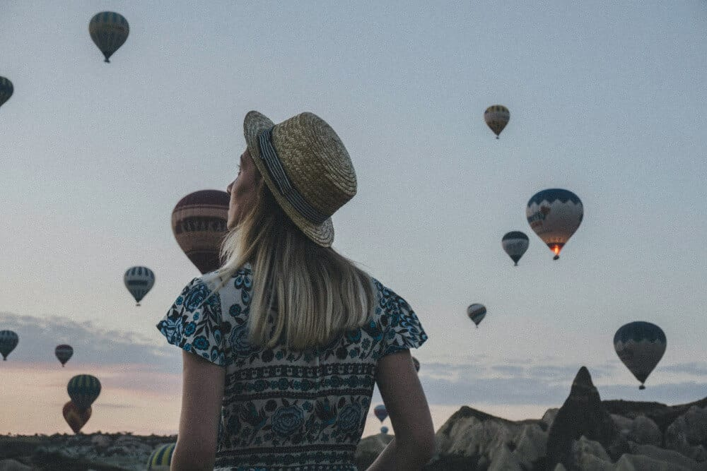 Woman over coming solo travel anxiety by watching the hot air balloons
