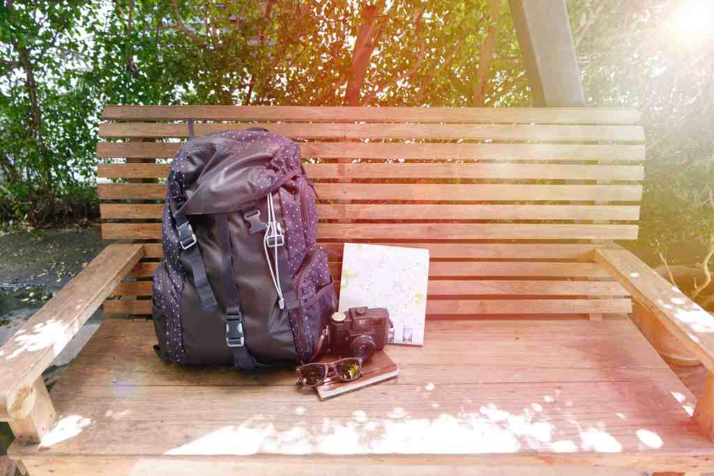 backpack on bench with camera