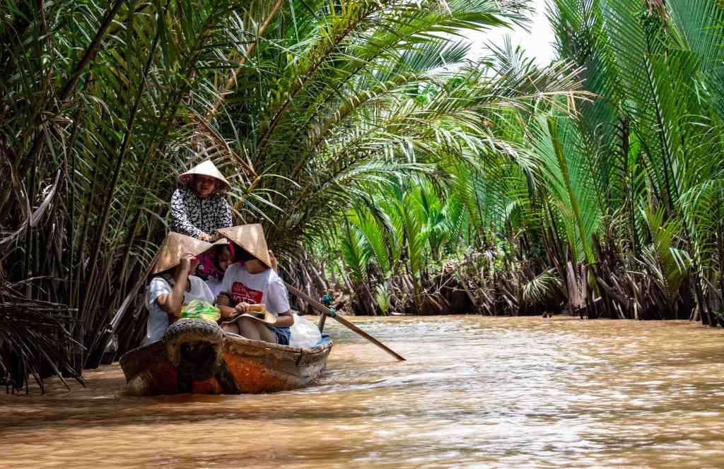 people travelling by boat down a river in Vietnam.