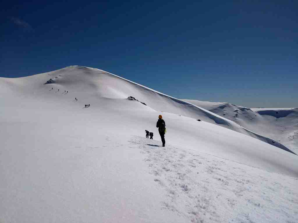 Tongariro Crossing in winter before Blue Lake. A snow covered mountain with people walking up it and blue sky behind.