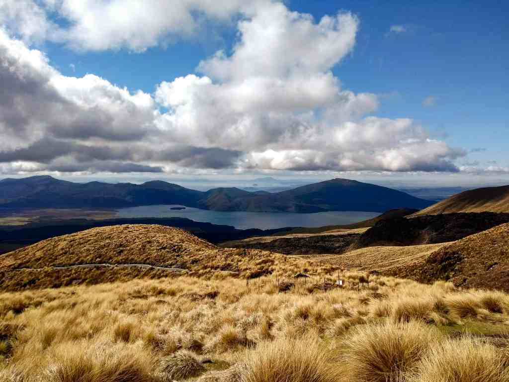 tongariro Crossing Ketetahi section. Hills and mountains in the background with a view of a lake.