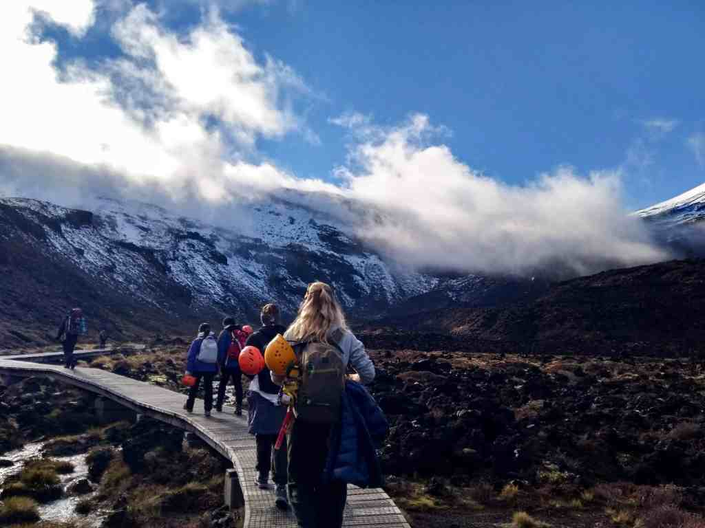 The start of the Tongariro Crossing in winter. People walking on the wooden walkway across marshland with mountains ahead.