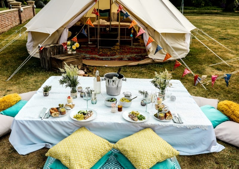 Luxury camping setup with a table, food and bell tent.