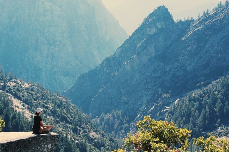 Person doing yoga in the mountains. A yoga retreat.