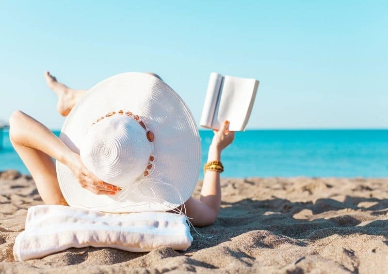 Ocean-friendly sunscreen is mineral-based. Person reading at the beach.