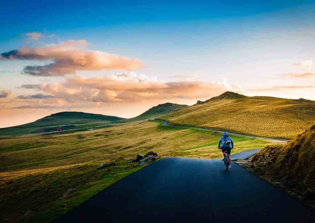 Person cycling through green hills.
