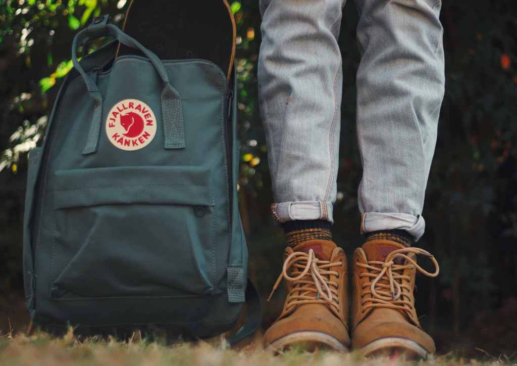 A Fjallraven kanken backpack next to a person wearing boots. An eco-friendly travel bag.