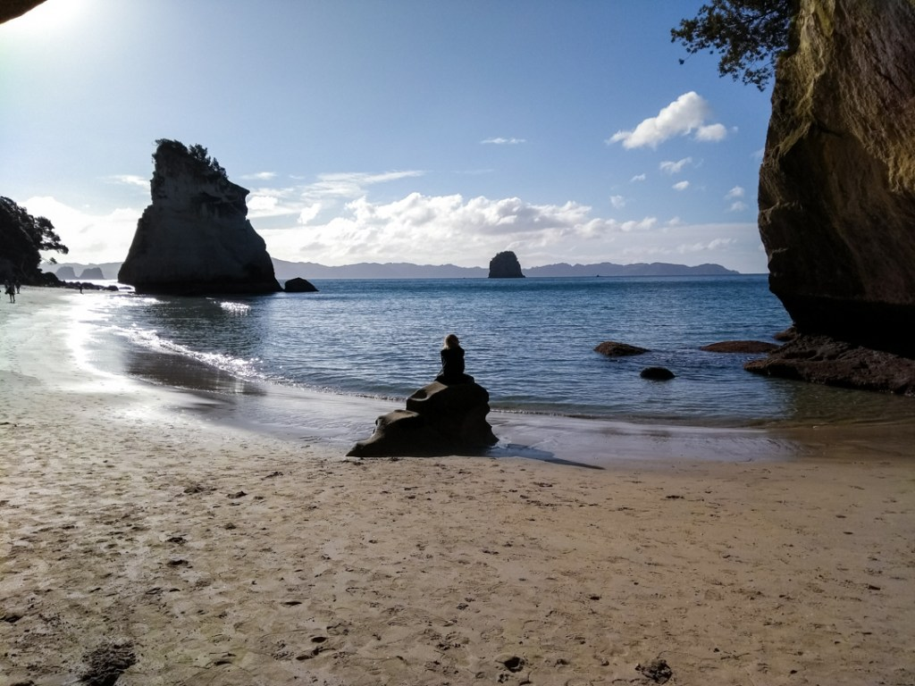 Girl sitting on a rock in front of a coastline with rocks in the sea in the background - cathedral cove