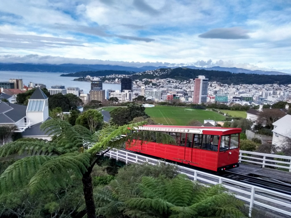 Red cable car in the foreground with a view of Wellington in the background.
