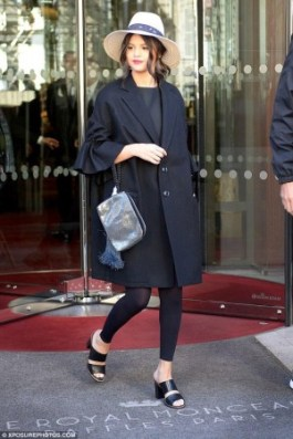 Accessories reign supreme in this final look by Selena. A simple black ensemble is taken to the next level with a pair of peek-a-boo shoes, a bold clutch, and a darling black and white, wide brimmed hat. Proof that you don't have to go completely over the top to create an impact with your look.