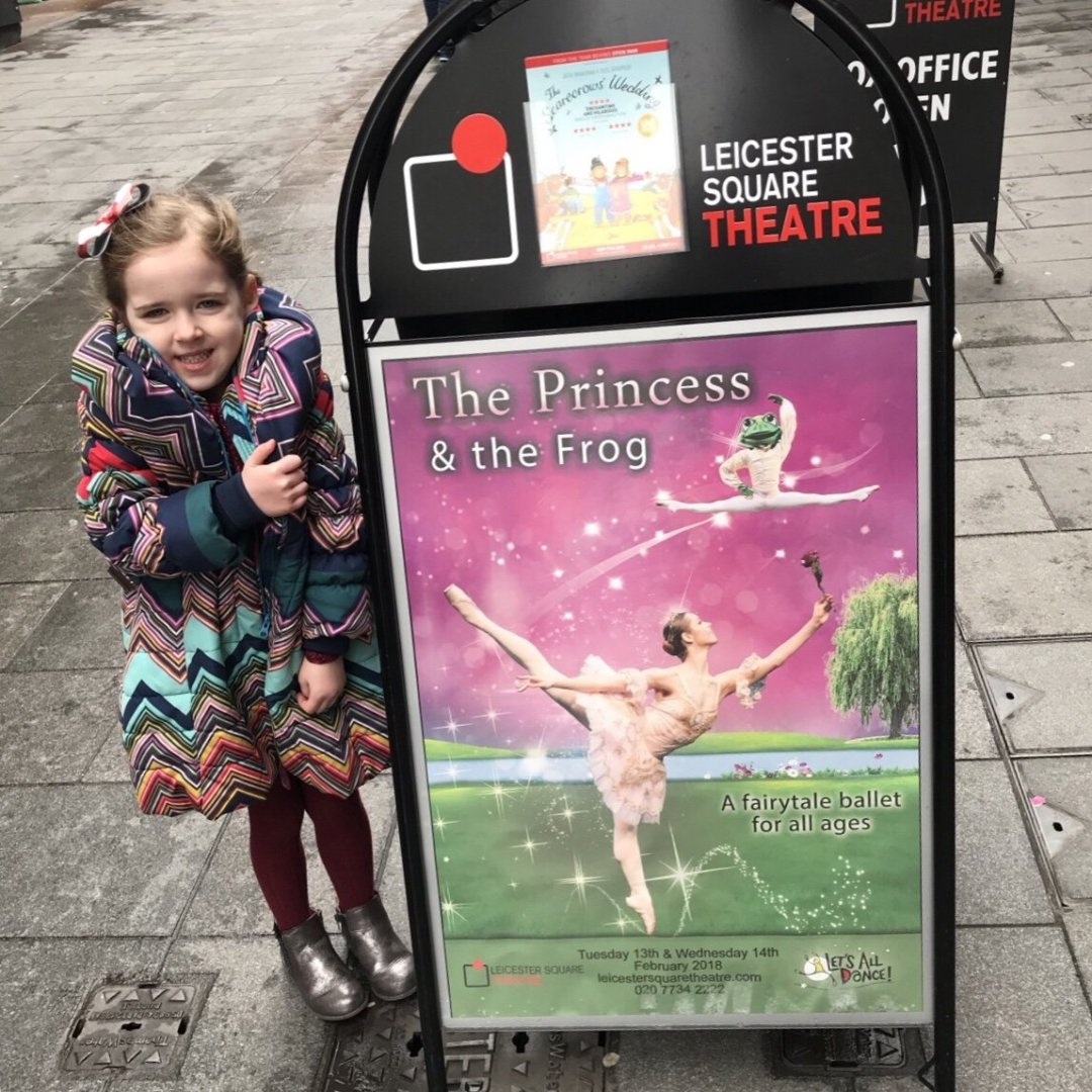First ballet, Eden standing with The Princess and the frog sign outside the theatre