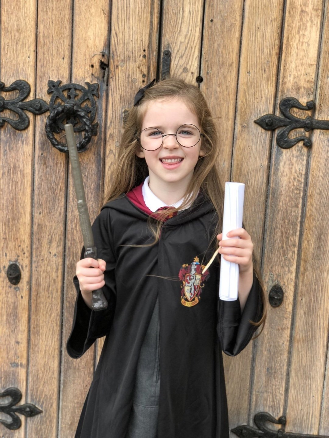 Child dressed as Harry Potter holding a wand