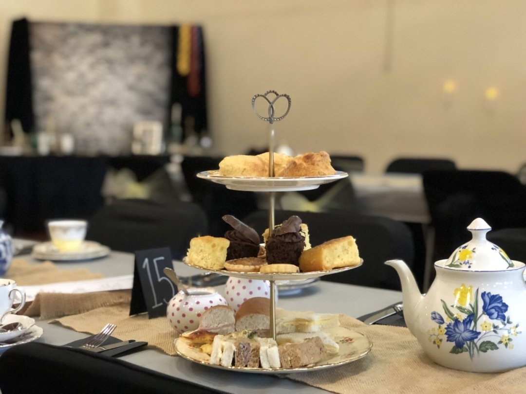 Cake stand and tea pot with Harry Potter themed backdrop a magical themed afternoon tea