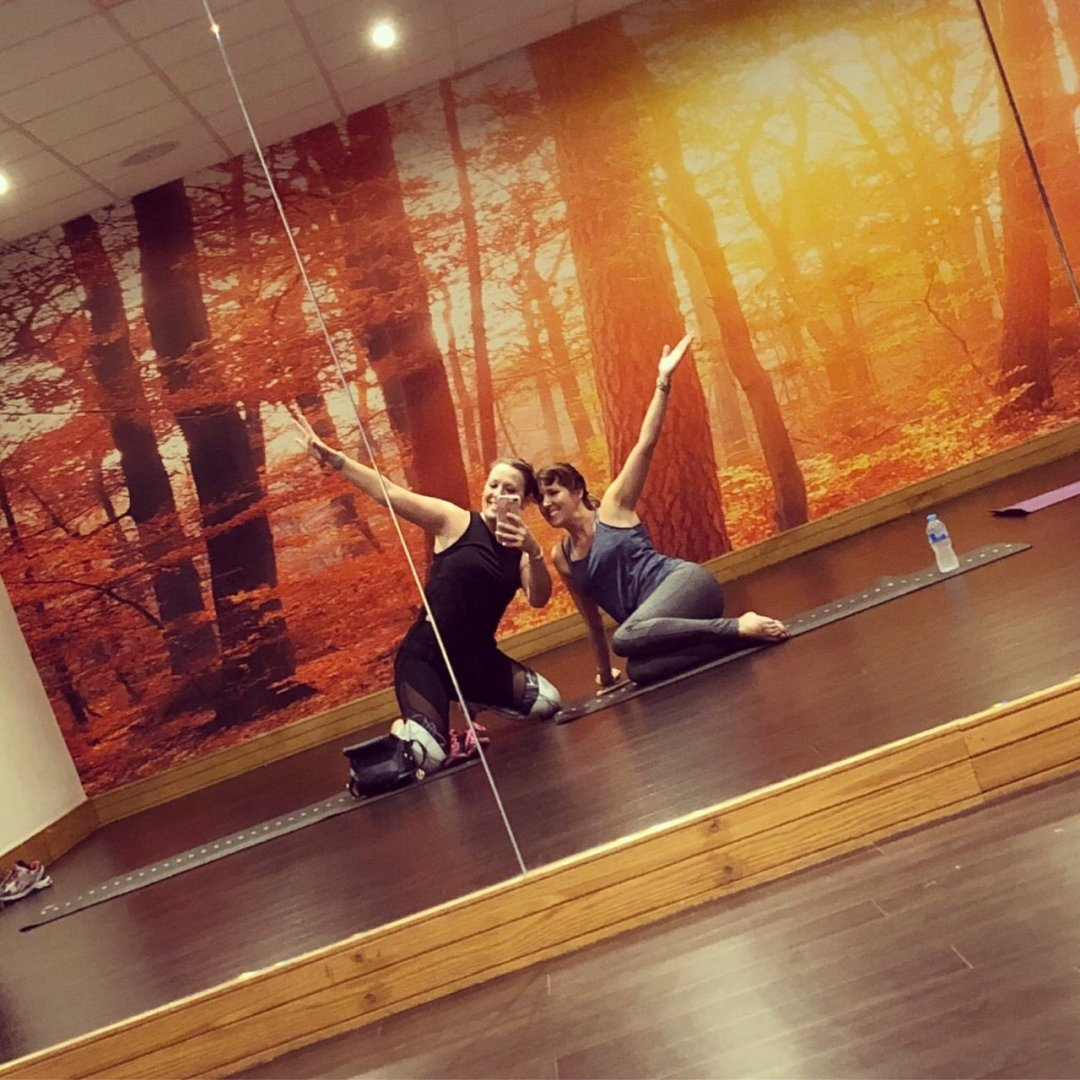 Two girls a yoga pose, keep motivated at the gym