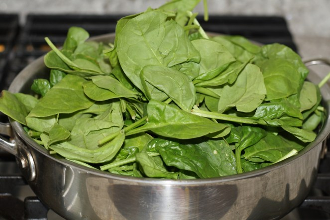 Baby spinach in a stainless steel pan
